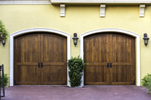 Side by side wooden garage doors that  can be installed by Semper Fidelis Garage Doors